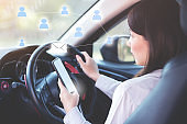 Woman send E-mail by smart phone while on a car