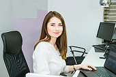 Portrait of skilled administrative manager working on laptop computer in office satisfied with occupation, young female receptionist organizing working schedule. Selective focus, space for text.