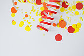 Bright festive decor. Red, yellow confetti, the serpentine on a white background