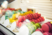 Assortment of Colorful macarons for sale in shop. Rows of macaroons in candy shop, storefront with sweets, cafe showcase. Traditional french almond cakes pastry. Variety of flavours. Selective focus.