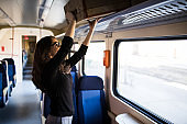 Woman putting her baggage on train grid compartment lifting commuter