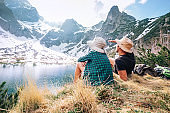 Father and son backpackers sit near the mountain lake and enjoy mountain snowy peaks