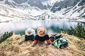 Father and son backpackers rest near the mountain lake and enjoy snowy peaks. Spring-summer hiking
