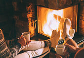 Couple in love drink a tea near fireplace. Cozy christmas home atmosphere