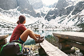 Woman traveler sits on rest point near mountain lake with beautiful view on snowy peaks