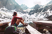 Woman traveler rests near mountain lake with beautiful view on snowy peaks