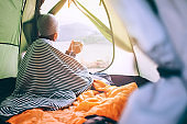 Alone Woman drinks hot tea in camping tent and enjoy with autumn evening in mountain valley