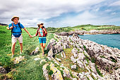 Couple backpacker travelers walk on ocean rocky coast. Asturias. Spain