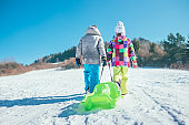 Little boy and girl carry the sled and enjoying winter sledding time