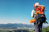 Woman traweler with backpack stay on the top of hill
