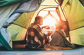 Father and son drink hot tea sitting together in camping tent