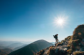 Boy backpacker traveler walk up on mountain top in contrast sun light