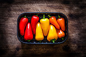 Colored peppers in a row in a plastic container