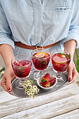 Anonymous hands holding tray of glasses of sangria for her guests