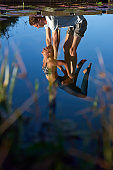 Artistic reflection on water of young couple doing yoga together
