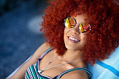 Portrait of beautiful woman with afro by the pool