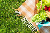 Green grass and straw basket with food and drinks on checkered beige tablecloth background for picnic, top view
