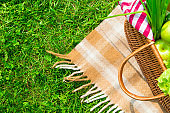 Green grass and straw basket with food on checkered beige tablecloth background for picnic, top view
