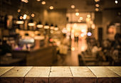 Wood table top (Bar) with blur light bokeh in dark night cafe,restaurant background