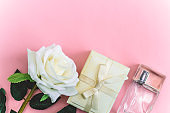 rose , gift box and perfume bottle on   a pink background copy space