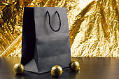 black package and shiny golden christmas balls