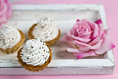cute vanilla cupcakes on vintage wooden tray