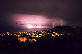 lightning strikes in the sky against the night city