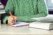 woman in  green sweater holding pen,  table with  notebook and  book