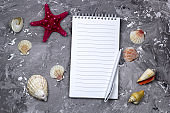 notebook with empty sheet, pen and sea shells
