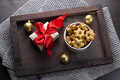 present with red bow, cookies in a shape of stars and golden christmas balls