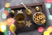cookies in a shape of stars,tea cup  ,honey jar and golden christmas balls