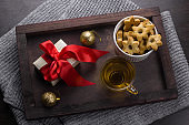 present with red bow, cookies in a shape of stars,tea cup   and golden christmas balls