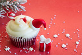 Christmas cupcake holiday ornament with fir and gift on red abstract background