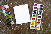 old used watercolor paint palette, old vintage brushes and blank white sheet of paper