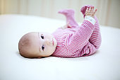 Beautiful baby playing with his legs on the bed in bedroom.