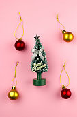 small toy decorative christmas tree top view on pink pastel background