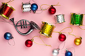 christmas decorations horn and drums top view on a pink pastel background