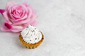 top view vanilla cupcake and blurred rose