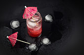 top view glass jar with red cocktail and ic