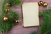old empty paper sheets and fir green branches with christmas golden balls