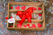top view wooden box with paper hearts and present with red bow and label