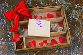 top view wooden box with paper hearts and present with red bow and empty old paper sheet