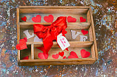 top view wooden box with paper hearts and present with red bow