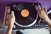 man puts a vinyl record in the player