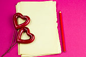 empty white sheet of paper and pen with pen and two red hearts