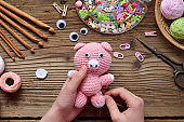 Making pink pig. Crochet toy for child. On table threads, needles, hook, cotton yarn. Step 2 - to sew all details of toy. Handmade crafts. DIY concept. Small business. Income from hobby