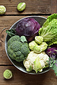 Different varieties of cabbages on wooden background. Organic fresh vegetables - cauliflower, kohlrabi, broccoli, purple cabbage. Raw food. Healthy food