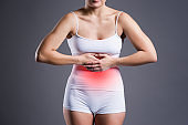 Woman with abdominal pain, stomachache on gary background