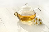 Chamomile tea in a glass teapots and white daisy flowers on a white wooden board background.Organic teas for health