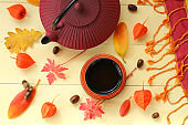 Autumn tea drinking. burgundy textured teapot in Asian style,cup of tea, physalis, yellow leaves, acorn on yellow wooden background.Autumn season.